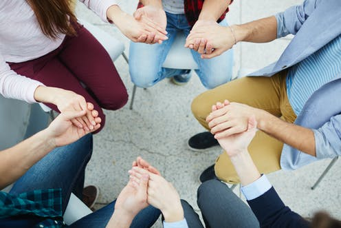 People sitting in a circle, holding hands