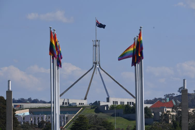 Rainbow flags flying against background of Parliament House, Canberra