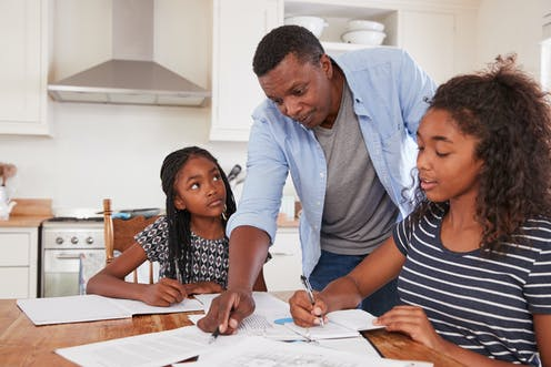 Father pointing out something to two daughters doing their schoolwork