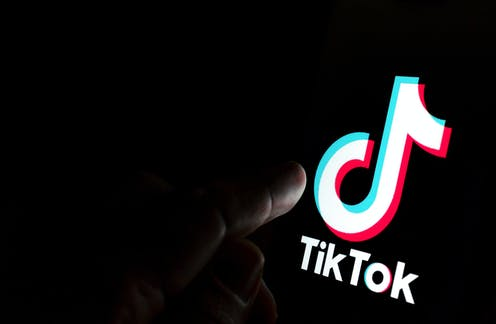 The TikTok symbol is displayed on a phone screen.
