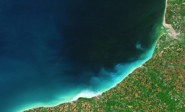 Vue du ciel, végétation et habitations sur la côte, mer et sédiments dans l'eau.