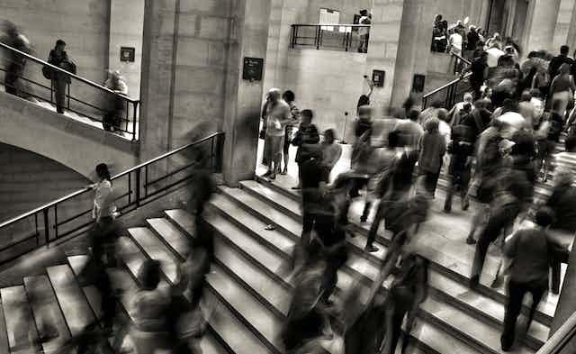 Des gens montent et descendent des escaliers, effets floutés.