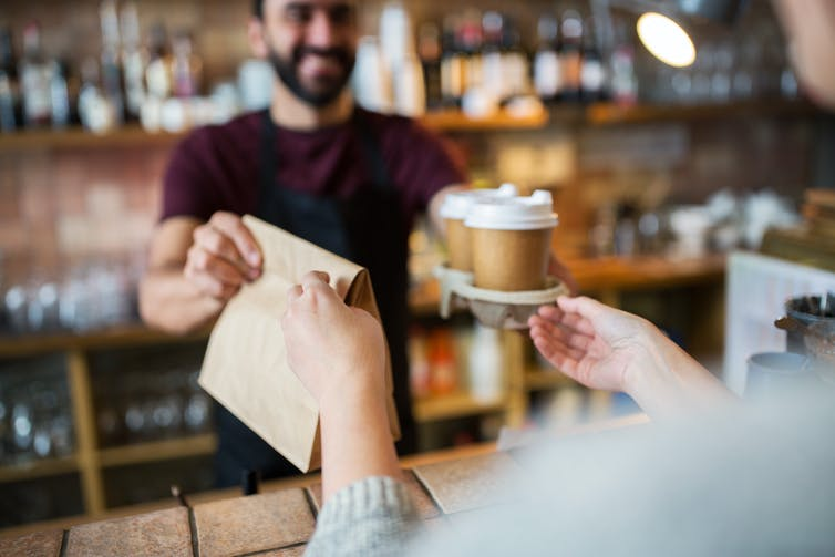 Barista hands takeaway coffee and bag to customer.