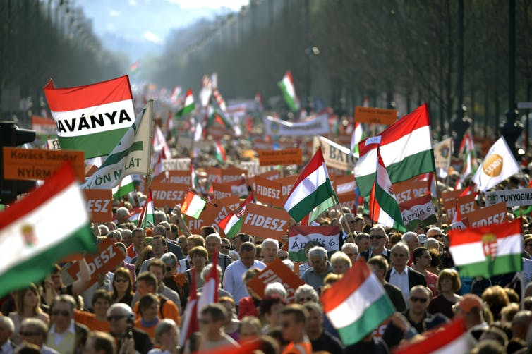 A crowd waves Hungarian flags.