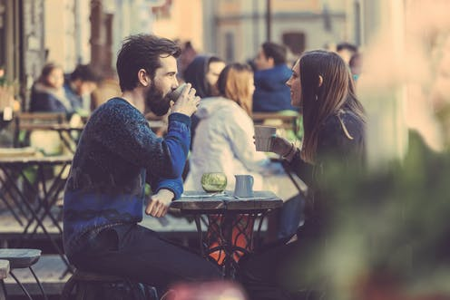 Couple drinking coffee at an outside table.
