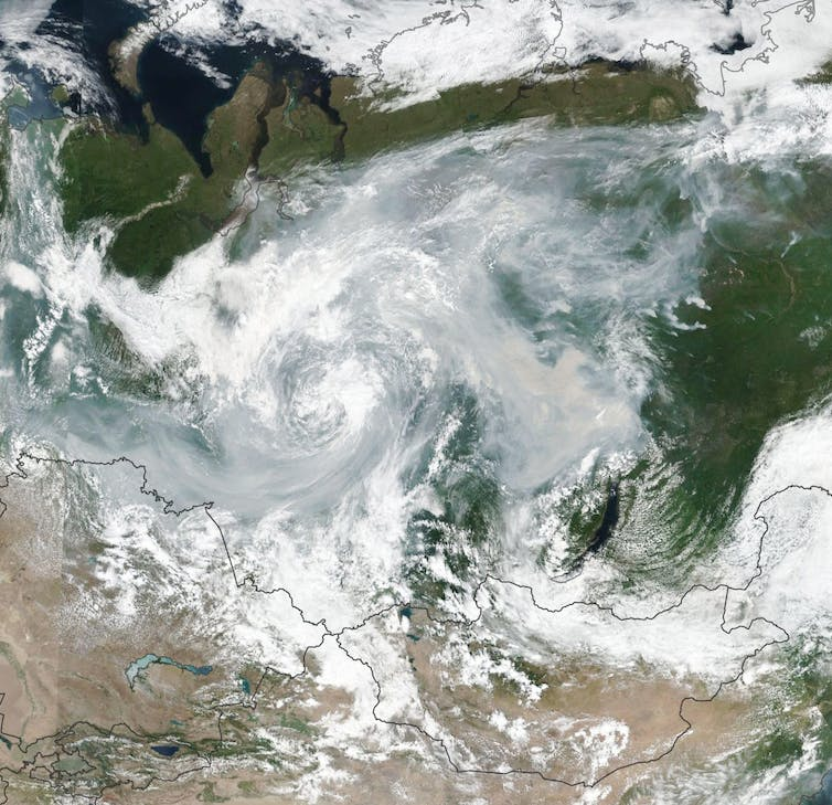 A satellite image shows smoke and clouds swirling over Russia.