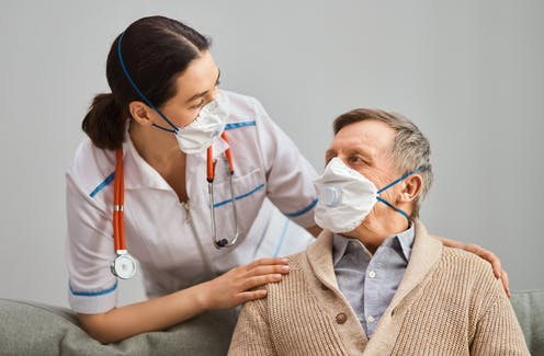 An older man, wearing a mask, interacting with a nurse