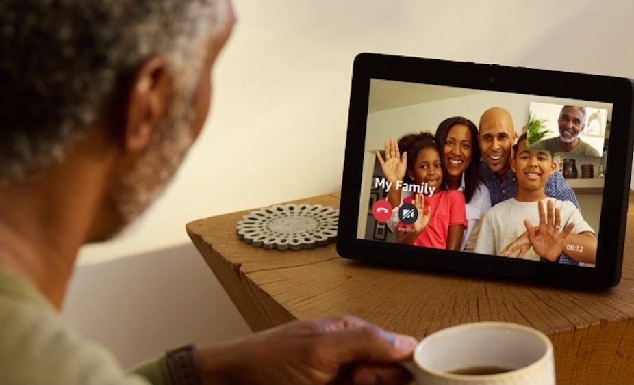 Man watching Amazon Echo Show drinking coffee