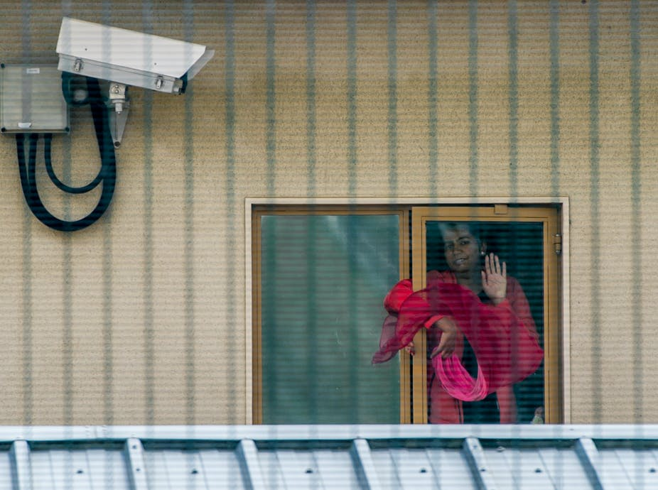Woman at window of detention centre.