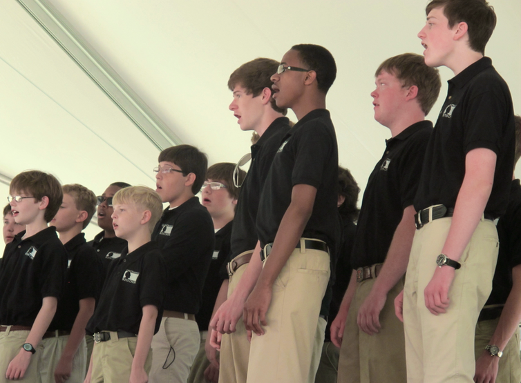 Ten boys ranging in age from roughly eight to 16, stand facing the same direction singing.