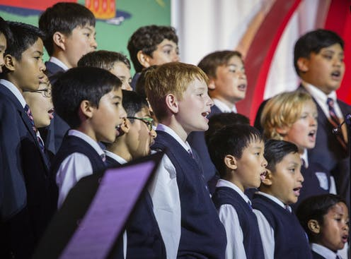 A medium shot of a boys choir, mid song. The boys are wearing vests and ties.