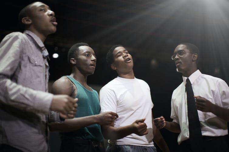 Four Black teen singing together.