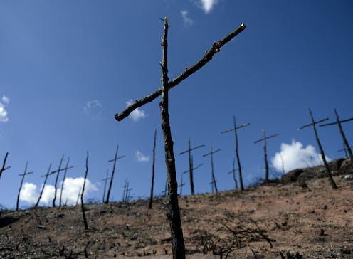 burned stick crosses on a bare hillside