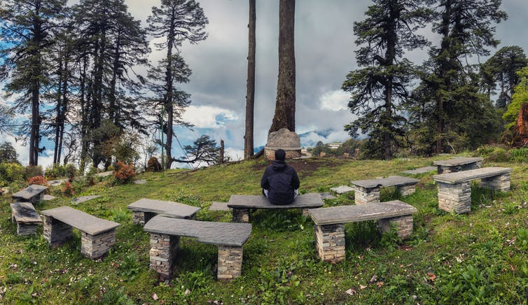 person seated on stone bench in outdoor preaching area
