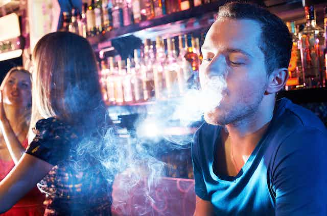 A smoker in a busy bar.