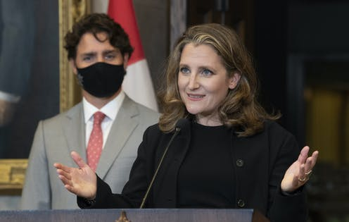Chrystia Freeland gestures while talking to the media with Justin Trudeau standing behind her wearing a mask.