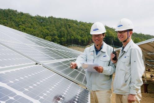 Two men inspect a sollar array