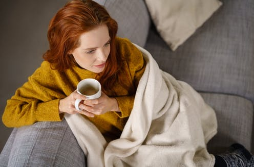 Young woman sitting on sofa wrapped in a blanket drinking a mug of tea
