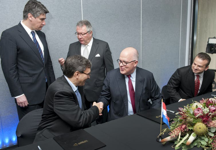 Men in business suits shake hands over an agreement