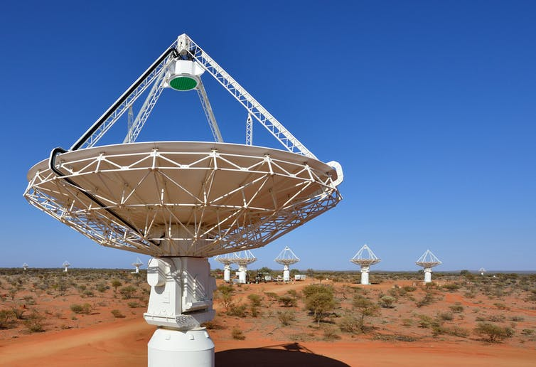 Antennas and a satellite dish in the foreground, with others in the background, in the WA desert.