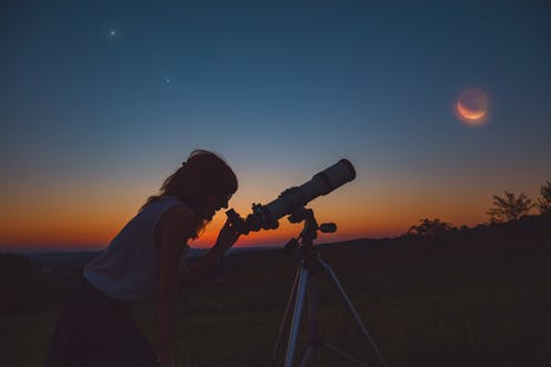 Silhouette of woman looking through a telescope at dusk.