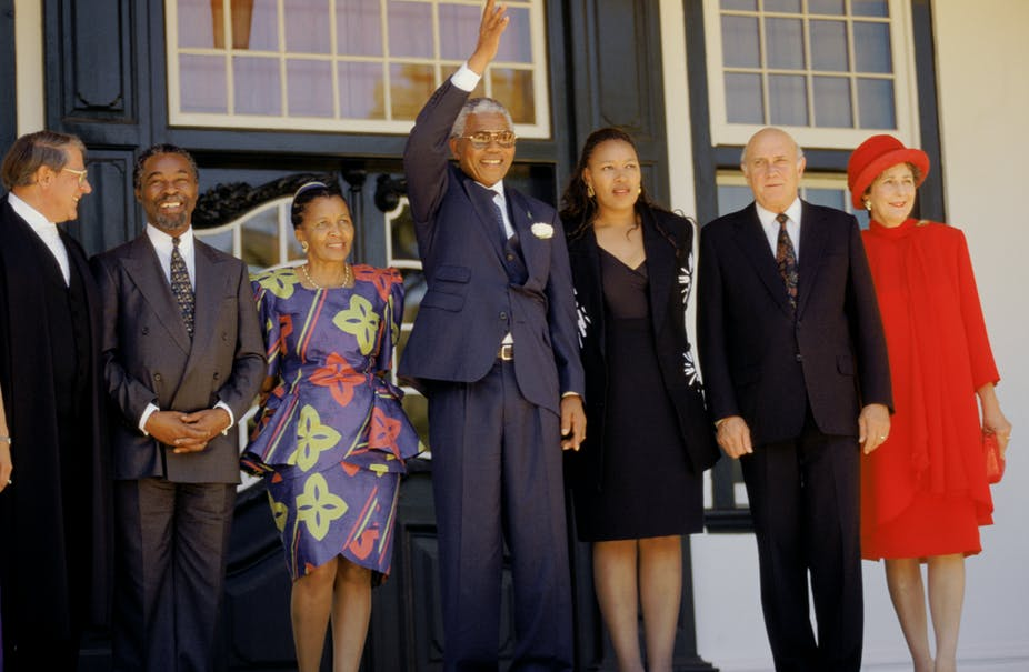 A grey-haired Nelson Mandela wearing a navy blue suit and specs waves his right hand, flanked by  Apartheid-era Justice Minister Kobie Coetsee, Thabo and Zanele Mbeki,  Zenani Mandela as well as  FW and Marike de Klerk.