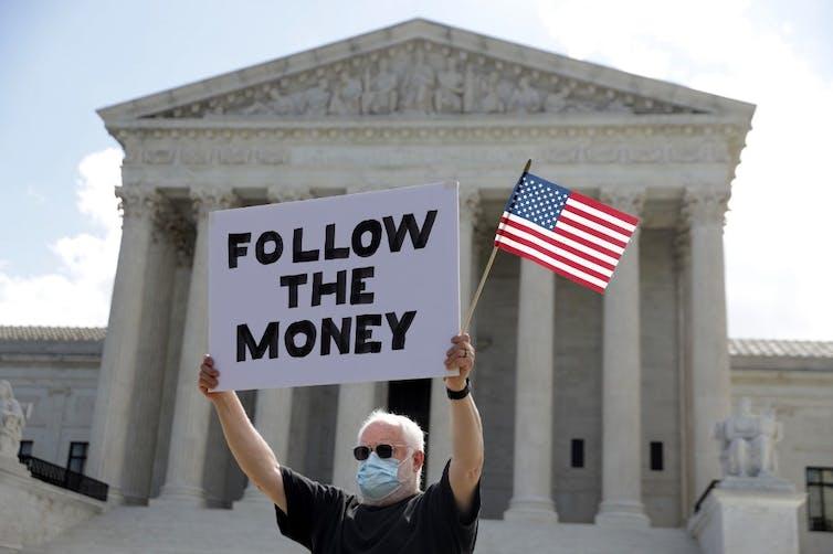 Homme tenant une pancarte devant le bâtiment de la Cour suprême.