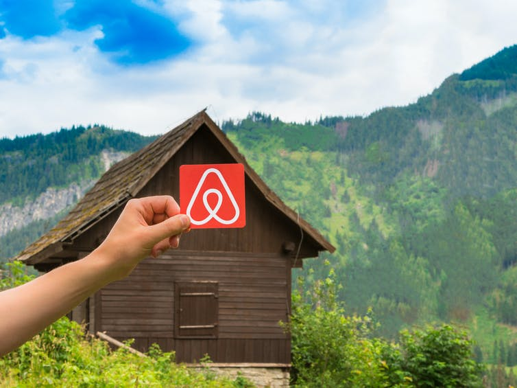 Airbnb logo held by a hand in front of wooden hut in countryside.