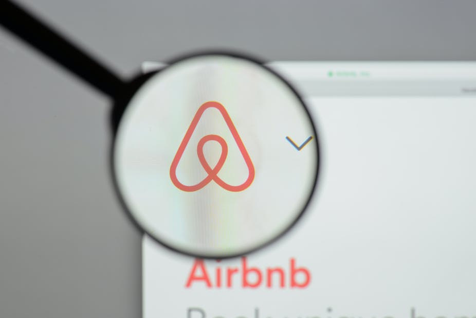 Airbnb logo behind a magnifying glass.