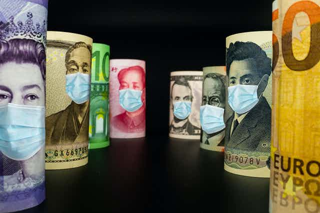 World currencies lining up with face masks on them