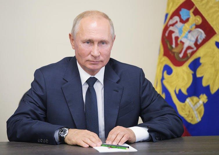 Vladimir Putin net to a flag.