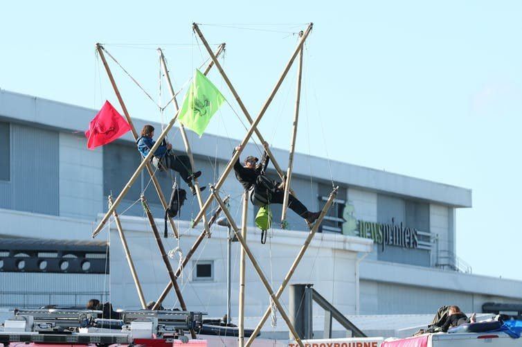 Two protesters are suspended in bamboo towers erected in front of a newspaper printing plant.