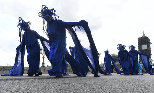Protesters in blue dresses march down Westminster Bridge in London, UK.