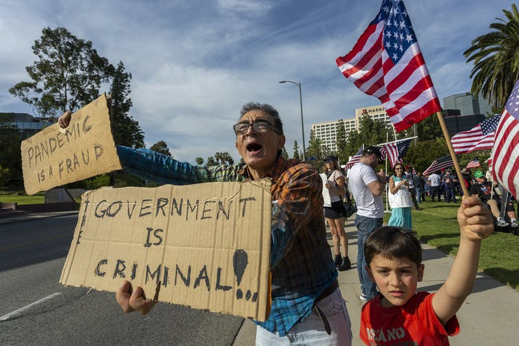 A man holds a sign saying 'government is criminal' and 'pandemic is a fraud' next to a child waving an American flag