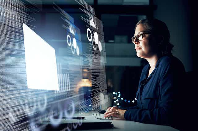 Woman typing in front of massive computer screen full of programming code.