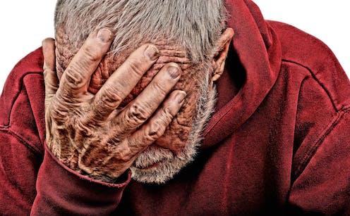 Un hombre mayor se tapa la cara con un gesto de desesperación