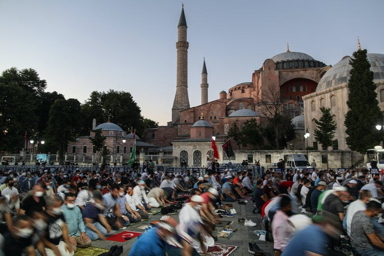 Many people pray in front of Hagia Sofia.