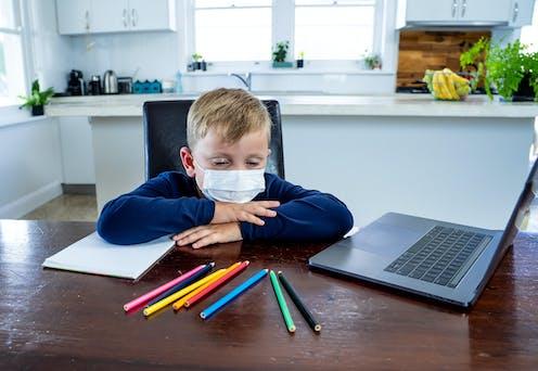 Un niño solo, con mascarillas, dormita en la mesa de la cocina de su casa ante unos lápices de colores y un ordenador de sobremesa.