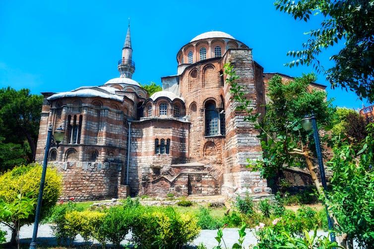 Stone Byzantine church under blue sky.