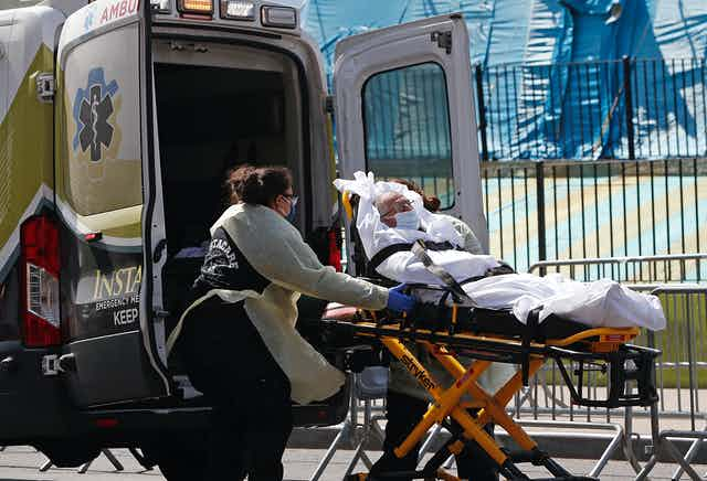 An older man being wheeled on a gurney into an ambulance. i