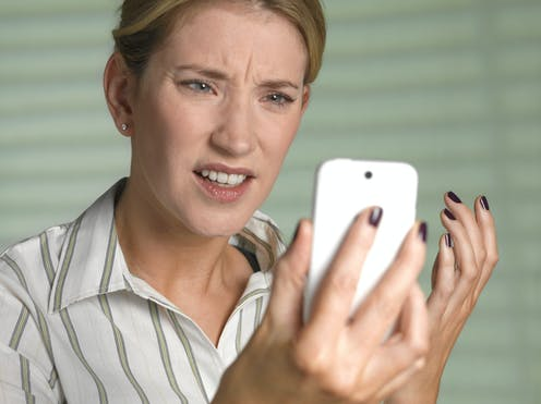 Annoyed woman looking at a smartphone