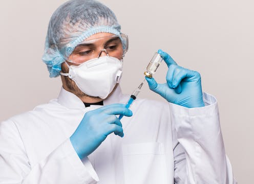 A man in a mask and lab coat filling a syringe with fluid