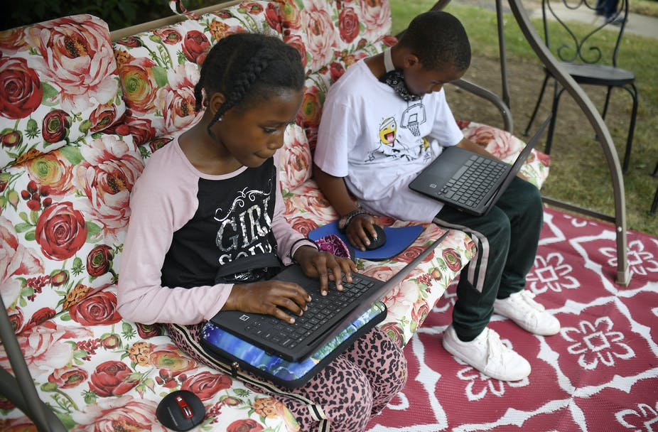 Two children do their schoolwork on laptops.