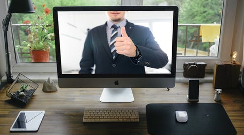 A man gives a thumb's up on a computer screen.