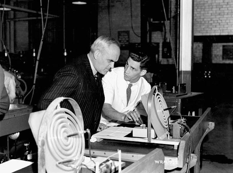 Two men lean over some scientific equipment.