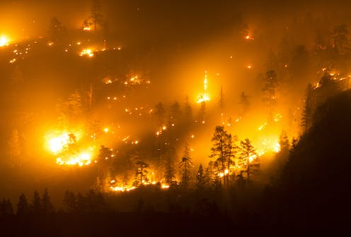 Flames burn up a mountain slope at night.