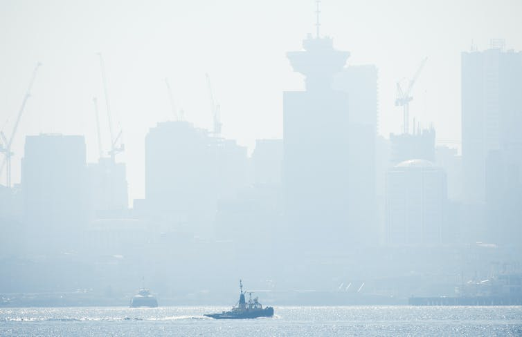 Smoky skyline with boat in the foreground.