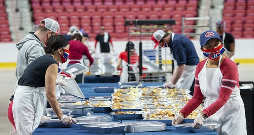 Four people wearing Montréal Canadiens face masks prepare containers of food with the red seats of a hockey arena behind them.