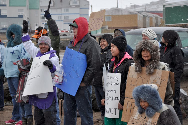 People wearing coats and hats hold up protest signs