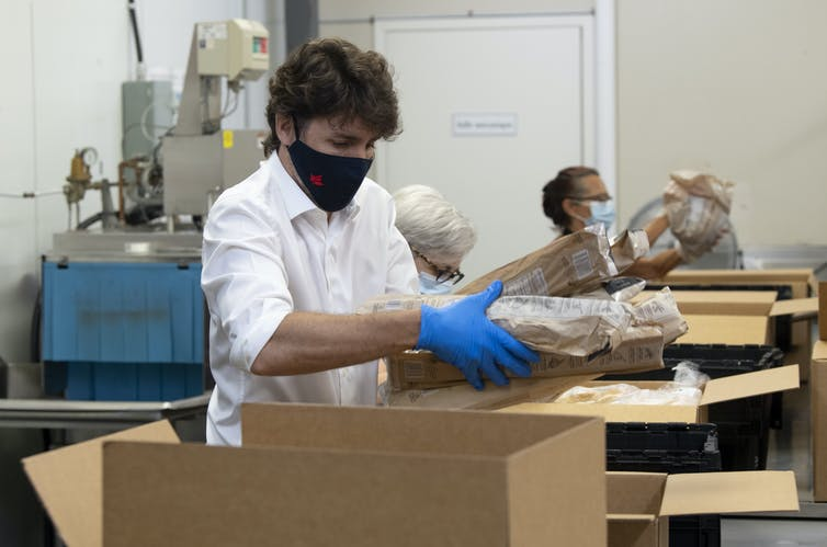 Justin Trudeau, wearing a mask and gloves, places items in a cardboard box.